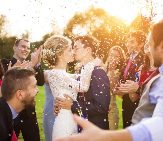 bruidspaar kussen met gasten